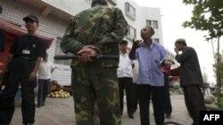 1 người sắc tộc Uighur cố gắng giải thích cho 1 bảo vệ Trung Quốc lý do ông bán dưa hấu trên lề đường ở Kashgar, tỉnh Tân Cương, Trung Quốc, 6/8/2008