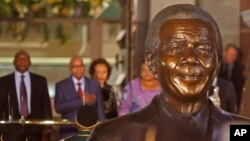 South African President Jacob Zuma, second left, in background with a bust of former South African President Nelson Mandela, center, outside Parliament before giving the State of the Nation address in the city of Cape Town, South Africa, June 17, 2014.