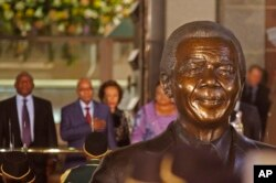 FILE - South African President Jacob Zuma, second from left behind a bust of former president Nelson Mandela, prepares to give a national address in Cape Town, June 17, 2014.