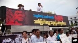 ນັກເຄື່ອນໄຫວຖືກປ້າຍໃນລະຫວ່າງການປະທ້ວງຕໍ່ການສັງຫານນັກຂ່າວອິດສະຫຼະ Aung Kyaw Naing ຢູ່ນອກຫ້ອງການລັດຖະບານໃນນະຄອນ ຢາງກຸ້ງ ປະເທດ ມຽນມາ. 26 ຕຸລາ 2014.