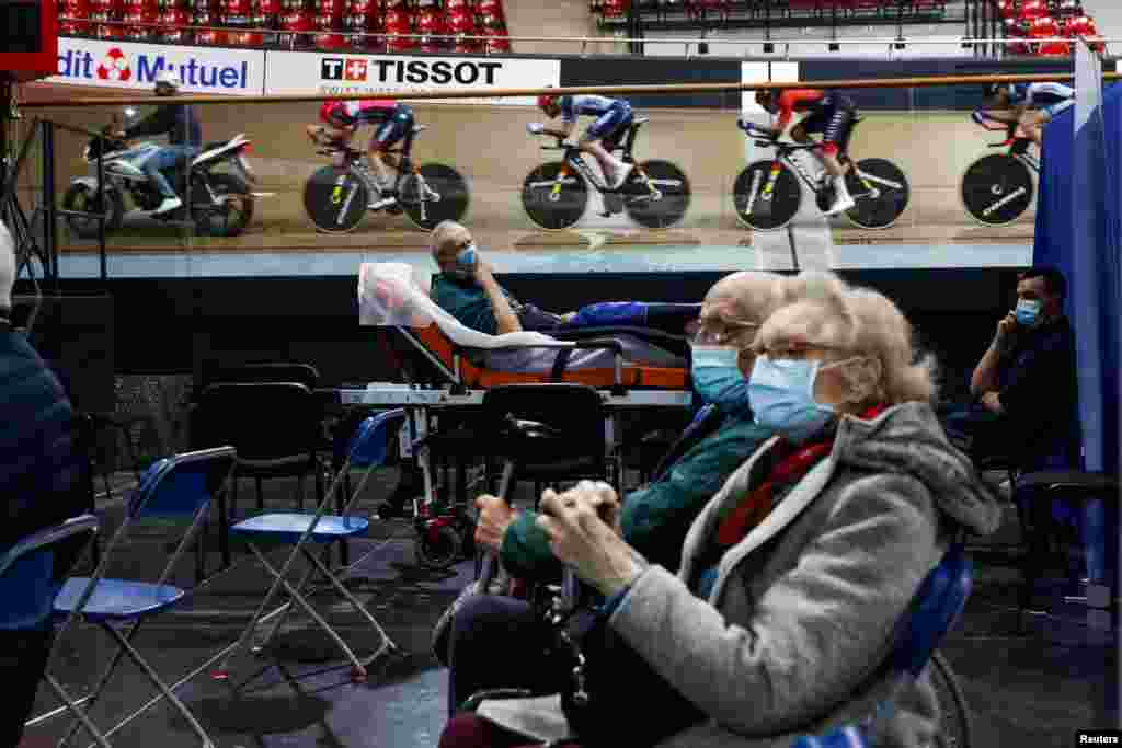 France's national cycling team trains as people wait to get a dose of the Pfizer-BioNTech COVID-19 vaccine at the indoor Velodrome National of Saint-Quentin-en-Yvelines in Montigny-le-Bretonneux, southwest of Paris, France.