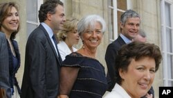 French Finance Minister Christine Lagarde, center, stands with ministers as she leaves the Elysee Palace in Paris, after the weekly Cabinet meeting, June 29, 2011