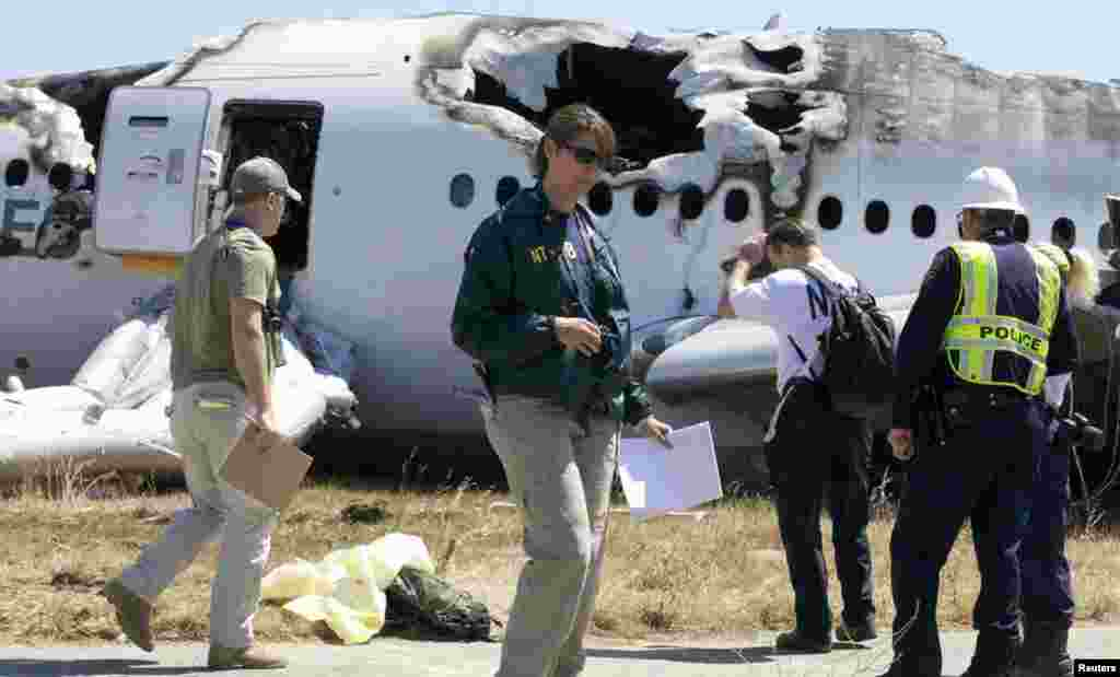 U.S. National Transportation Safety Board (NTSB) investigators stand at the scene of the Asiana Airlines Flight 214 crash site at San Francisco International Airport, July 7, 2013. (NTSB)