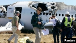 2013年7月7日,美国国家交通安全委员会(NTSB)调查人员站在旧金山飞机场韩亚航空公司客机失事的现场。