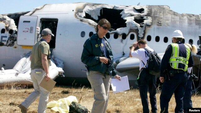 U.S. National Transportation Safety Board (NTSB) investigators stand at the scene of the Asiana Airlines Flight 214 crash site at San Francisco International Airport in San Francisco, July 7, 2013. (NTSB)