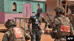French troops of the Sangaris Operation speak to a member of the Anti-Balaka Christian militia who handed over his arms, Bangui, Jan. 25, 2014.