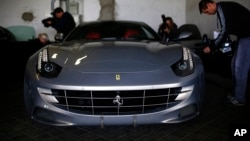Members of the media take images of one of the two Ferrari luxury cars donated by Spanish former King Juan Carlos to the National Heritage, in Madrid, Oct. 19, 2015.