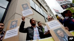 Men hold protest posters in front of a court to support the release of the journalist Ahmed Mansour in Berlin, Germany, June 21, 2015.