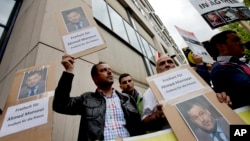 Men protest to support the release of the journalist Ahmed Mansour in Berlin, Germany, Sunday, June 21, 2015. Mansour, 52, a senior journalist with the Qatar-based broadcaster Al-Jazeera, was detained at Tegel airport on Saturday on an Egyptian arrest warrant.