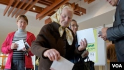 Warga Latvia memasukkan kartu suara di salah satu TPS di Jaunmarupe, Latvia (17/9).
