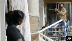 An Ethiopian maid, right, chats with another maid from Sri Lanka, left, as they stand on balconies in Beirut (File Photo)