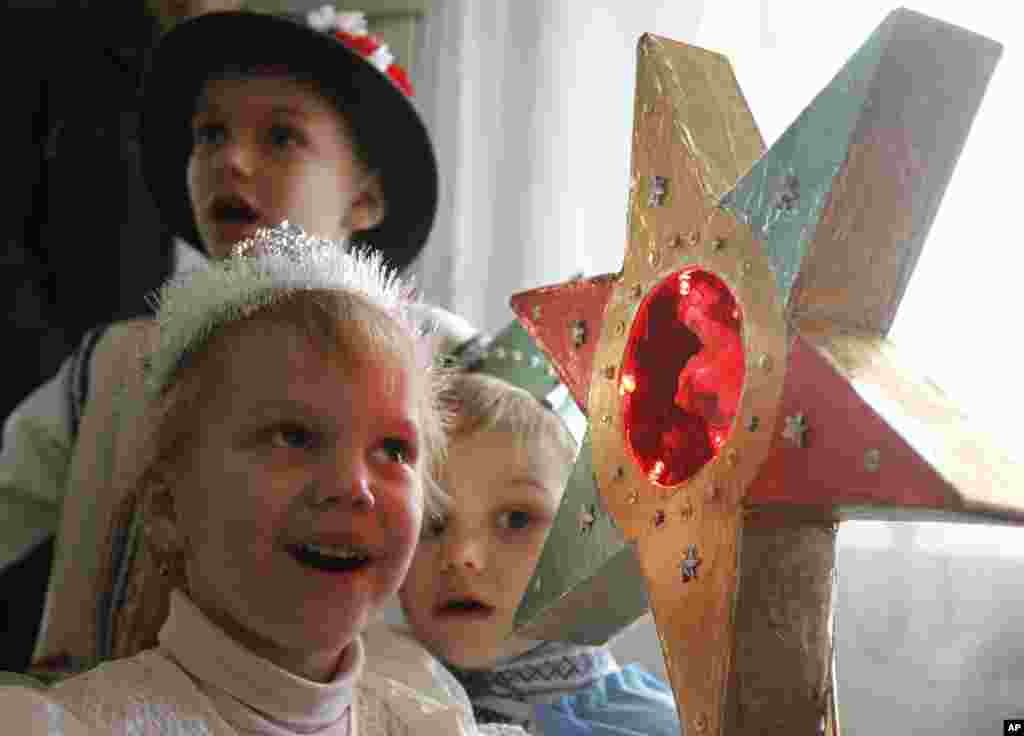 """Children in traditional costumes sing Christmas carols, known locally as """"Kolyadki"""" as they celebrate Orthodox Christmas in Pustomity village near Lviv, Urkaine, January 7, 2012. (Reuters)"""