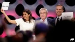 Ketua Komite Olimpiade Internasional (IOC) Thomas Bach (tengah) berpose bersama Walikota Paris Anne Hidalgo (kiri) dan Walikota Los Angeles Eric Garrett di markasa IOC di Lima, Peru, Rabu (13/9).