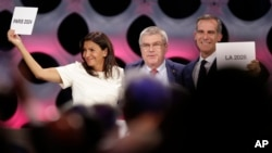 International Olympic Committee President Thomas Bach stands between Paris Mayor Anne Hidalgo, left, and Los Angeles Mayor Eric Garrett at the end of the IOC session in Lima, Peru, Sept. 13, 2017.