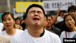 Thân nhân cách hành khách Trung Quốc trên chuyến bay MH370 phẫn nộ hô khẩu hiệu và khóc trong lúc tuần hành đến Đại sứ quán Malaysia tại Bắc Kinh, ngày 25/3/2014.