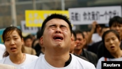 A family member of a passenger on board Malaysia Airlines MH370 cries as he shouts slogans during a protest in front of the Malaysian embassy in Beijing, March 25, 2014.