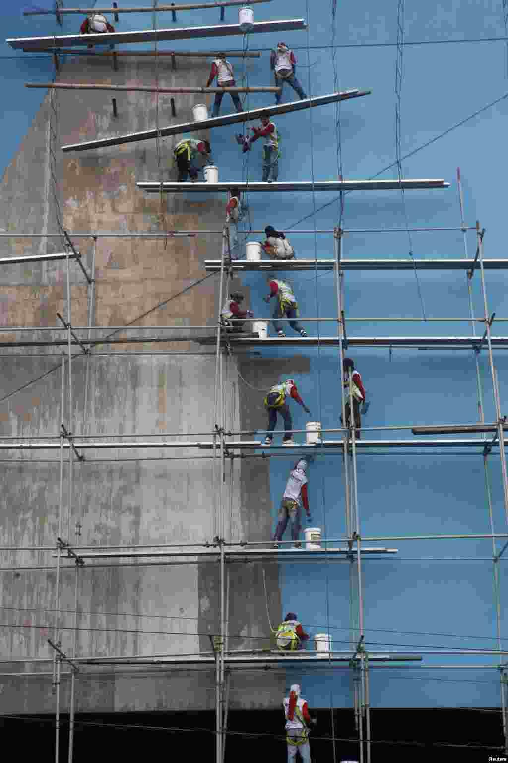 Workers paint the building of a new branch of SM mall, owned by Philippine tycoon Henry Sy, in Paranaque, metro Manila.