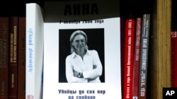 A portrait of investigative reporter Anna Politkovskaya with the words 'the killers are still at large' is displayed on a bookshelf in the offices of the Novaya Gazeta newspaper in Moscow, Russia, Oct. 7, 2021.