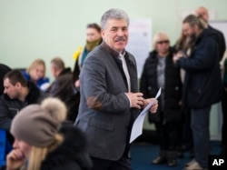 Communist party candidate Pavel Grudinin prepares to cast his ballot in the presidential election at the Lenin state farm outside Moscow, Sunday, March 18, 2018.
