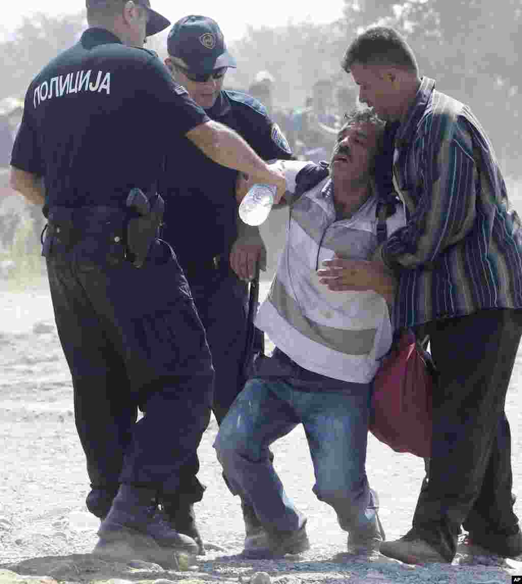 Macedonian policemen help a dehydrated migrant after crossing the border from Greece to Macedonia, near the southern town of Gevgelija.