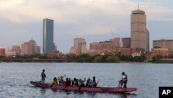 Un bote se desplaza a lo largo de Cambridge, Massachusetts, el lunes, 27 de julio de 2015, frente a Boston, después que el COI cortara vínculos con la ciudad.