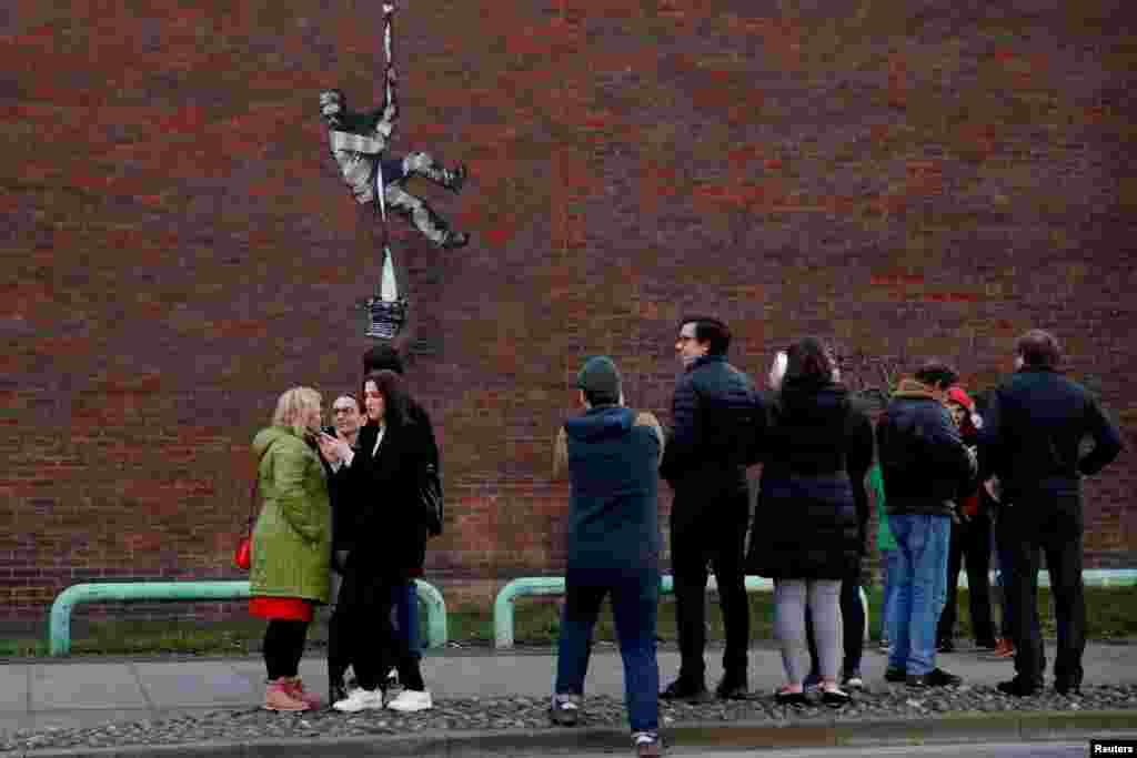 People look at of a mural by artist Banksy on a wall at HM Reading Prison in Reading, Britain, March 1, 2021.