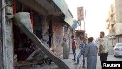 Warga setempat memeriksa sebuah toko yang hancur akibat serangan drone yang diduga milik Amerika Serikat dekat sebuah stasiun komunikasi di Raqqa (23/9).Sebuah drone menewaskan sedikitnya delapan tersangka militan di daerah Datta Khel di Waziristan Utara (24/9).