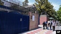 Pedestrians walk past the main gate of British Embassy in Tehran, Iran, Aug. 22, 2015.