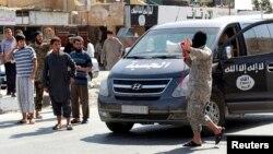 지난 24일 시리아 라카 지역에서 수니파 반군 '이슬람국가' 소속 병사가 북동부 군용기지를 점령했다고 마을 주민들에게 방송하고 있다.
