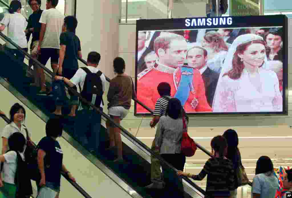 People in Thailand watch a live telecast of the wedding ceremony of Britain's Prince William and Kate Middleton at a shopping mall in Bangkok. (REUTERS/Chaiwat Subprasom )