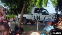FILE - A U.N. truck drives past displaced South Sudanese families resting in a camp for internally displaced people in the United Nations Mission in South Sudan compound in Tomping, Juba, July 11, 2016.