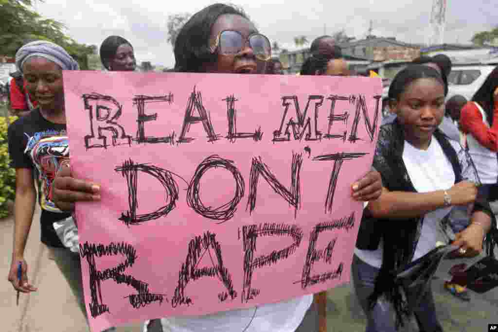 """A woman carries a placard as she shouts a slogan during the """"walk against rape'"""" procession organised by """"Project Alert"""", a Lagos-based NGO focusing on women's issues, in Nigeria's commercial capital Lagos."""