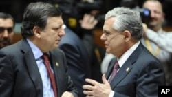 European Commission President Jose Manuel Barroso, left, speaks with Greek Prime Minister Lucas Papademos during a round table meeting at an EU summit in Brussels, January 30, 2012.