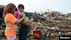 Anak-anak di Moore, Oklahoma, menenangkan anjing mereka setelah tornado melanda daerah tersebut Senin (20/5).