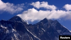 Cloud rise behind Mount Everest, the world's highest peak at 29,029 ft., viewed from Kongde, near Namche Bazar, Nepal, March 5, 2009.