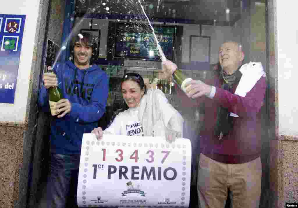 """Lottery seller Raquel Carrasco (C) holds a sign with the winning number of Spain's Christmas Lottery """"El Gordo"""" as employees spray champagne in La Eliana near Valencia. The total prize money of 2.4 billion euros is split into thousands of cash prizes among hundreds of winning numbers."""