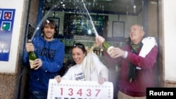 "Lottery seller Raquel Carrasco (C) holds a sign with the winning number of Spain's Christmas Lottery ""El Gordo"", as employees spray champagne in La Eliana near Valencia December 22, 2014. The total prize money of 2.4 billion euros is split into thousands"