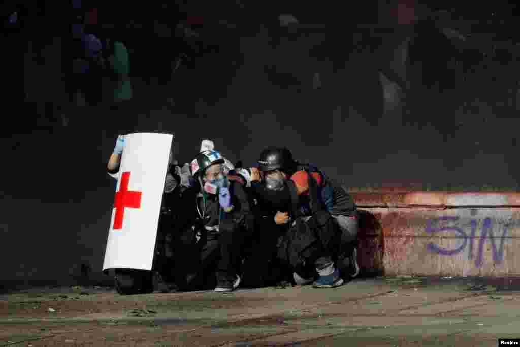 Members of a first aid team and a photographer take cover during an anti-government protest in Santiago, Chile, Oct. 28, 2019.