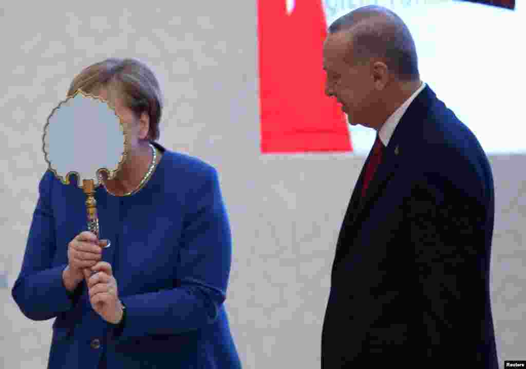 German Chancellor Angela Merkel receives a gift from Turkish President Tayyip Erdogan during the official opening ceremony of Turkish-German University's new campus in Istanbul, Turkey.
