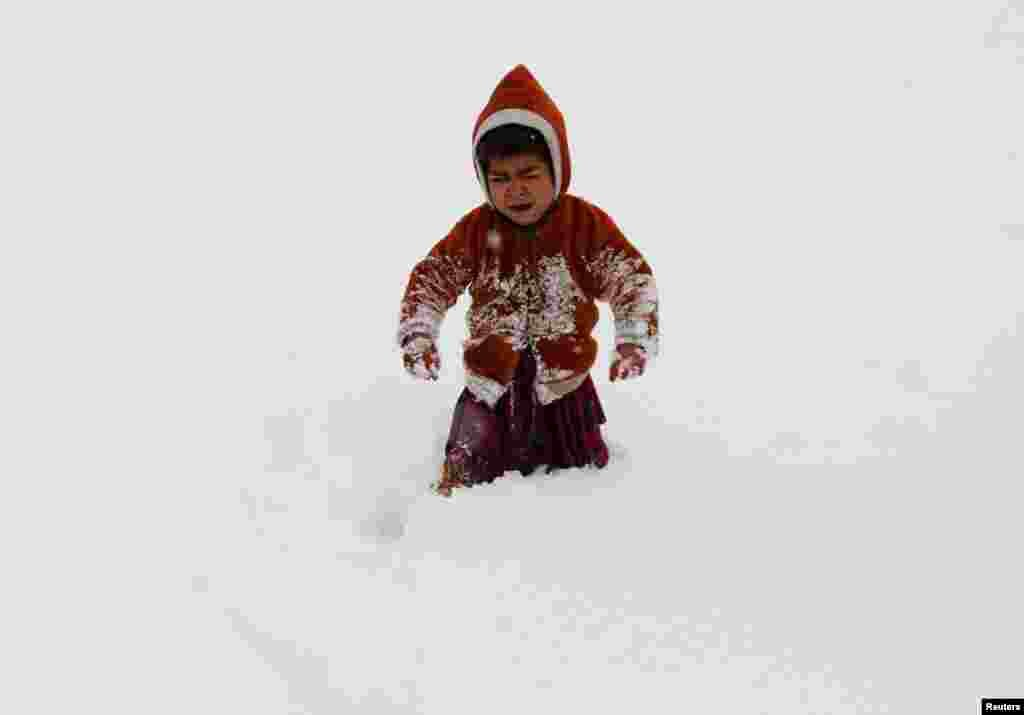 An internally displaced Afghan child cries as he gets stuck in waist-deep snow outside his shelter during a snowfall in Kabul.