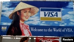 FILE - Tourists walk past advertisements of foreign companies near the airport of Ho Chi Minh City (formerly Saigon) March 8, 1994.
