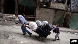 Người dân kéo hành lý rời khỏi khu vực Sheikh Maqsud ở Aleppo, Syria, 4/42013
