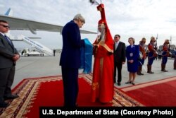 U.S. Secretary of State John Kerry accepts a gift of aaruul -- dried cheese curds -- from a woman in traditional Mongolian dress greets as he arrives at Chinggis Khaan International Airport in Ulaanbataar, Mongolia, June 5, 2016.
