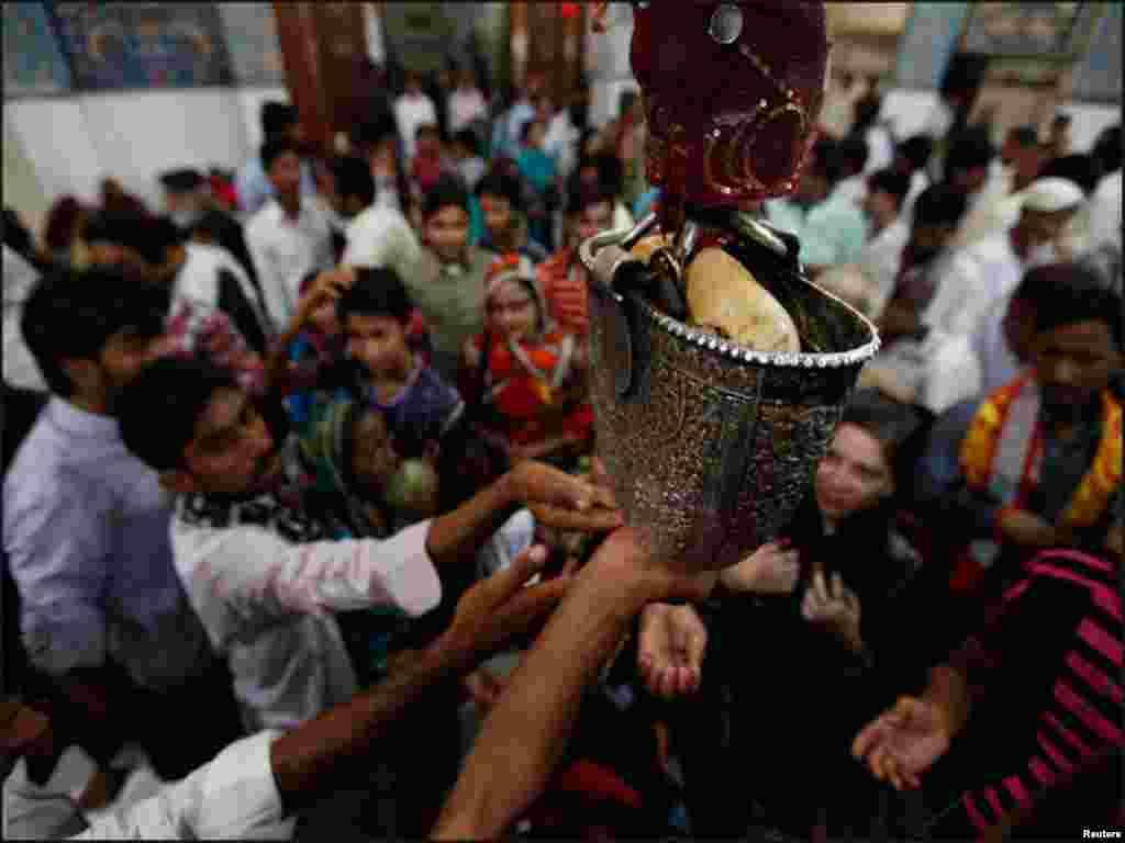 لعل شہباز قلندر کے مزار کے احاطے میں لگے سلور کے ایک برتن سے گزرنےوالے مقدس پانی کو عقیدت مند ہاتھ میں لینے کی کوشش کررہے ہیں۔