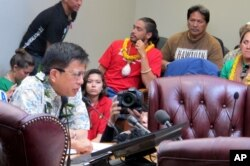 In this file photo, University of Hawaii law professor Williamson Chang, front left, testifies against the Thirty Meter Telescope project during an Office of Hawaiian Affairs meeting in Honolulu on April 4, 2015, as Lanakila Mangauil, background center, l