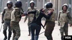 Pasukan keamanan Mesir menangkap demonstran anti-pemerintah di Kairo (23/12). Mesir setuju untuk menghentikan penggerebekan atas kantor LSM pro-demokrasi.