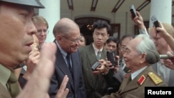 Former U.S. Secretary of Defense Robert McNamara, left, who helped direct America's War in Vietnam, shakes hands with Vietnamese General Vo Nguyen Giap, right, commander of the North Vietnamese Army in Hanoi on Nov. 9, 1995.