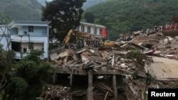 2014年8月5日,鏟土機在雲南昭通魯甸縣的地震災區現場清除廢墟,尋找遇難者遺體。