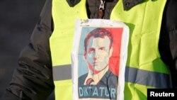 """Sarı jiletli"" etirazçı altında almanca ""diktator"" yazılmış Fransa prezidenti Emmanuel Makronun şəkli ilə."