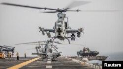 Pesawat AH-1Z Viper dari Tiltrotor Squadron (VMM) 163 (Reinforced), 11th Marine Expeditionary Unit (MEU) bersiap menaikii kapal penyerang amfibi AS, USS Boxer (LHD 4), saat transit di Selat Hormuz, Oman, 12 Agustus 2019. (Foto: AL AS via Reuters)